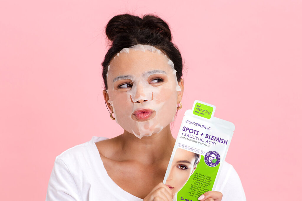 Girl pouting wearing mask holding Spots Blemish pack